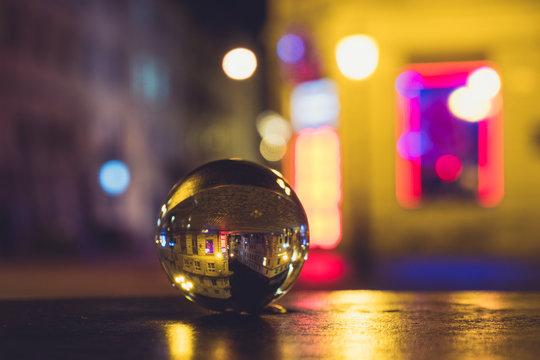 night city street blurred background through crystal glass ball