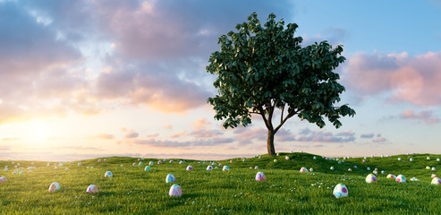 Many colorful Easter eggs lie in a meadow around a tree for Easter with dramtic sunset sky