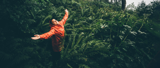 The young woman with orange raincoat smiles and laughs under the rain. Girl enjoying warm summer rain at the tropical forest. Сoncept of nature and happy life with adventure.