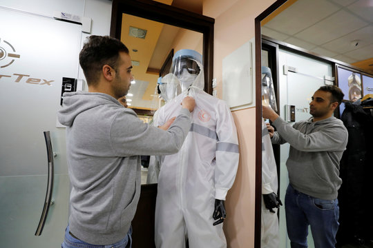A Palestinian man tries on a protective medical suit in a sewing factory amid precautions against coronavirus, in Hebron in the Israeli-occupied West Bank