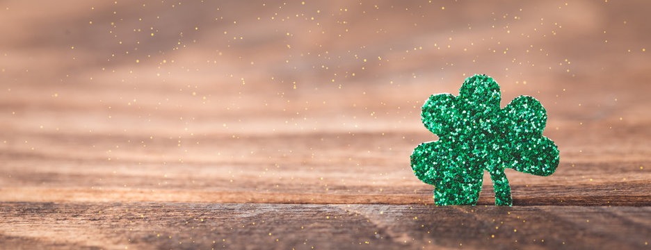 St Patrick's day background with shamrock clover leaf on wood, Irish festival symbol, selective focus