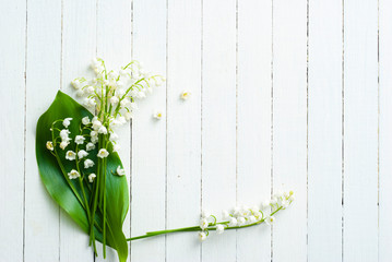 Fotobehang Lelietje van dalen Lily of the valley on white wooden