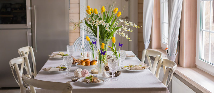 Easter festive spring table setting decoration, eggs in nest, fresh yellow tulips, marshmallows, selective focus banner