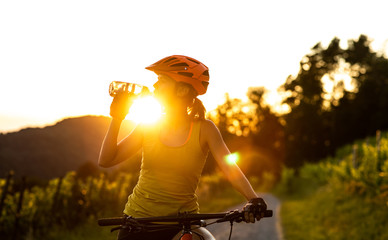 Pretty, young woman biking on a mountain bike enjoying healthy active lifestyle outdoors in summer (shallow DOF) Fototapete