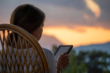young woman reading ebook with sky and mountains in the background