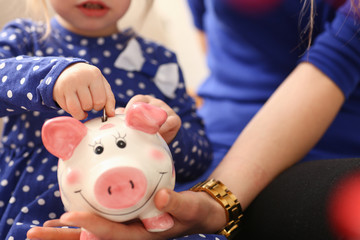Child little girl arm putting pin money coins into happy pink faced piglet slot closeup. Making effective future needs savings collect dollar gift benefit present home leisure concept