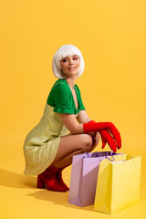 happy pop art girl in white wig with shopping bags, on yellow