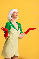 attractive smiling pop art girl in white wig with soap bubbles, on yellow