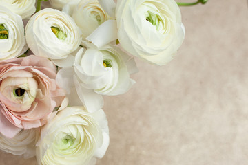 Elegance ranunculus bouquet on the sparkling background. Beautiful and tender flowers composition. Perfectly for Birthday, Women's and Valentine's Day, Anniversary. Copyspace. Top view.
