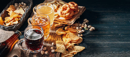three glasses of expensive craft beer, classic and unfiltered and dark in a glass on the table with a snack of peanut and pistachio chips and nachos
