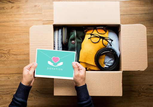 Donation concepts with person holding direct mail card on accessories clothing in box.giving and sharing with human