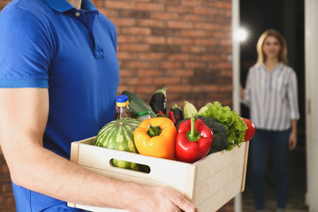 Courier with fresh products indoors, closeup. Food delivery service