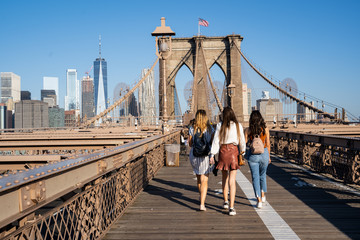 Zelfklevend Fotobehang Brooklyn Bridge Three girls walking on the Brooklyn Bridge with the New York skyline on the back