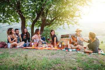 Picnic in the countryside - Group of young friends at sunset on spring day are sitting on the ground in a park near trees - They drinking red wine and eating grilled meat with barbecue and play guitar
