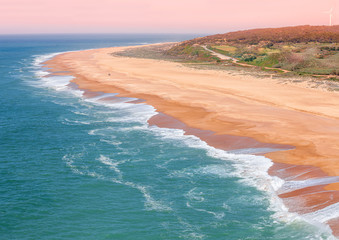 Fototapete - Sandy rocky seashore at sunset light. Seascape in the evening. Nazare, Portugal, Europe