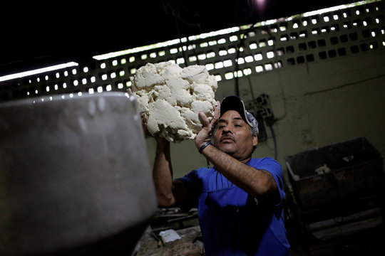 An employee loads dough to make tortillas at a tortilla stall in Nuevo Laredo