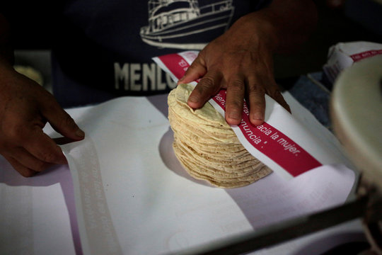 An employee wraps tortillas in paper with contact information to help women victims of gender violence, as a part of a government program called Break the Silence, at a tortilla stall in Nuevo Laredo