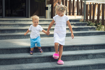 Two cute adorable caucasian blond little siblings walking down stiars residential building. Reliable elder sister support, learnd and help younger toddler brother. Family love, care support