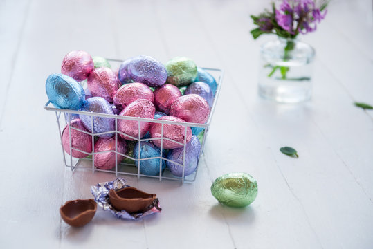 A metal modern basket filled chocolate easter eggs in multicolor foil on a white wooden table. Minimalist festive spring composition. Soft selective focus, copy space.