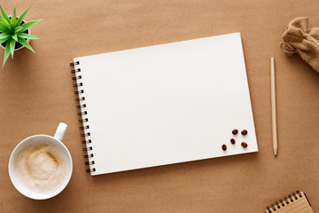 Cappuccino coffee on a brown empty background. View from above. Copy space with space for text. Mockup. Foam on coffee, white cup, scattered coffee beans, open sketchbook, succulent and jute bag.
