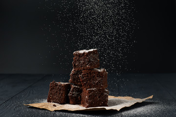 Stack of a brownie pieces on a grey table with dark background with sugar powder snow.
