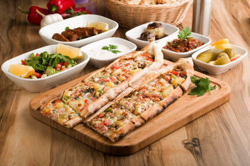 Foto op Canvas Assortiment Turkish vegetable pide on wooden table