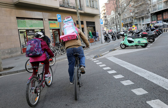 A father carries the backpack of his daughter as they ride their bicycle home after Catalonia announced to close schools, kindergartens, institutes and universities from tomorrow as a precaution against coronavirus in Barcelona