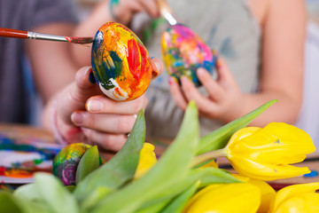 Woman and little girl paint Easter eggs by brush in different  colors. Seasonal decoration of eggs for holiday. Close up for hands.