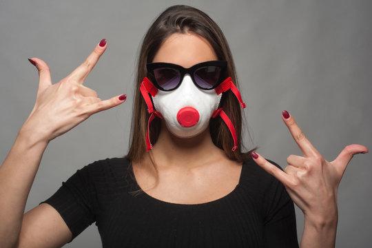 ragazza con mascherina e occhiali da sole che fa le corna