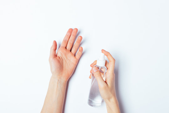 Woman's hands applying alcohol disinfectant spray