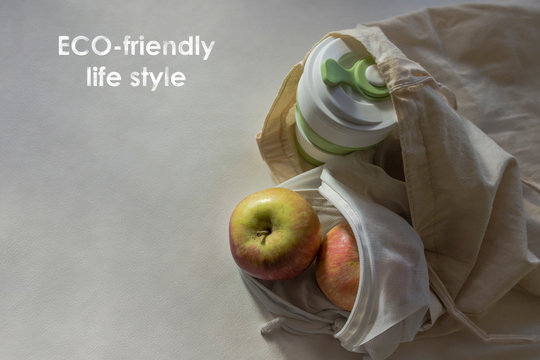 Shopper bag with collapsible silicone mug and apples in reusable fruit pouch