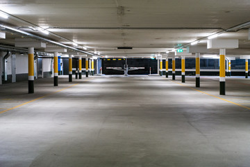 Inside underground large empty parking lot with barrier entrance at night illuminated by neon light Fototapete