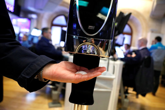 A trader uses a hand sanitizing dispenser as he works at the New York Stock Exchange (NYSE) in New York