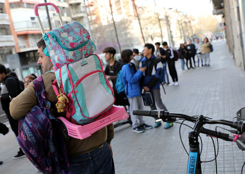 Father carries the backpack of his daughter as he waits for her at entrance of a school in Barcelona