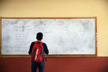 A student stands in front a slate at the Agustin Aspiazo School in La Paz