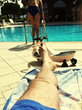 Low Section Of Man Resting At Poolside While Woman Diving Into Water
