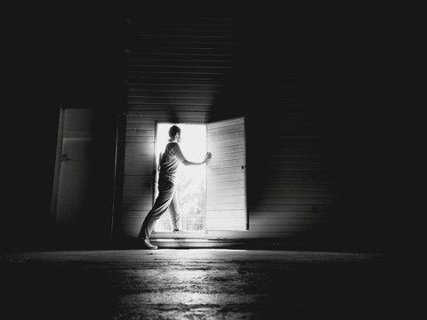 Side View Of Young Man Standing At Doorway In Darkroom