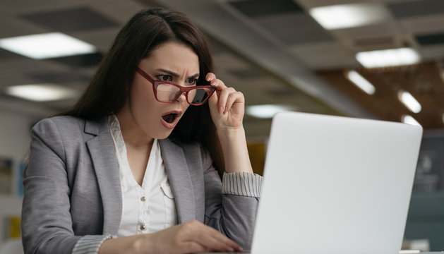 Portrait of shocked business woman in stylish eyeglasses using laptop computer , looking at digital screen. Emotional female with open mouth watching breaking news on website about coronavirus