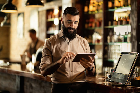 Smiling barista using digital tablet while working in a bar.