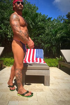Tattooed Man In Thong Standing By American Flag On Lounge Chair At Poolside