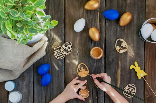 Happy Easter.Kids paints with paint balls and wooden crafts.Blue, Golden eggs on a rustic wooden background on a Sunny day.Spring holiday.DIY.Instructions. Preparing for the holiday.Flat lay