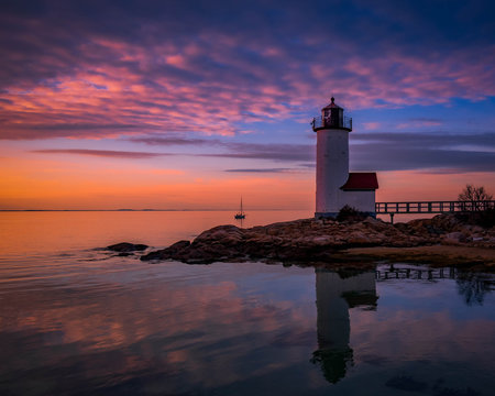 Sunset reflections at Annisquam Lighthouse with sail boat - Gloucester, Massachusetts.
