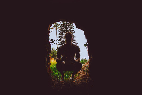 Silhouette Man Crouching At Entrance Of Cave