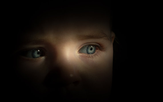 Close-up Of Boy Looking Away Against Black Background