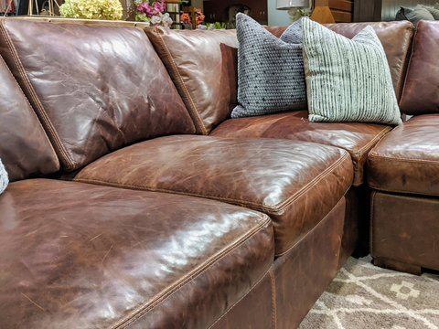 Close up of a leather sectional covered with pillows