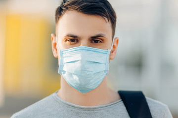 A young man in the background of an educational institution, with an anti-coronavirus mask on his face