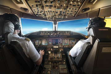 Fototapeta Rear View Of Pilots Sitting In Cockpit obraz