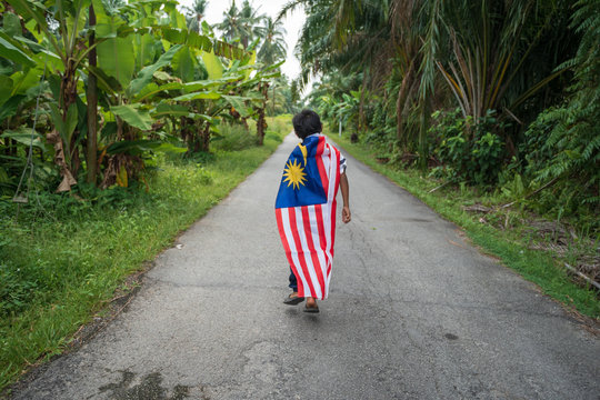 Rear View Full Length Of Boy With Malaysian Flag Walking On Road