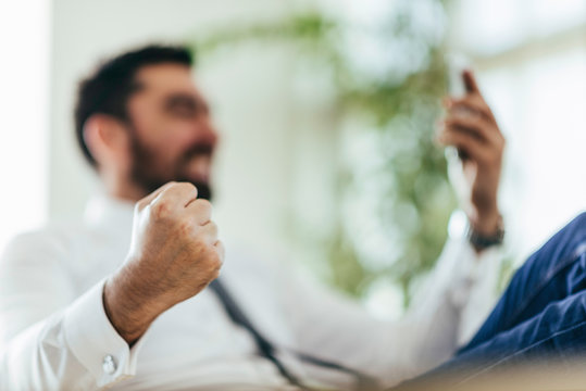 Low Angle View Of Businessman Clinching Fist While Using Mobile Phone