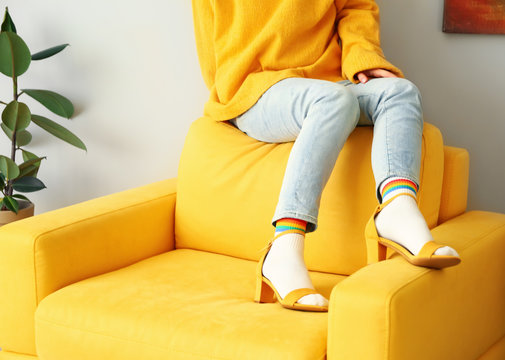 Young woman in socks and sandals at home